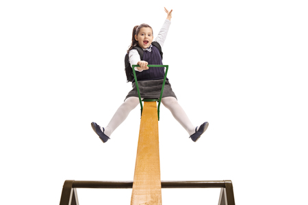 Joyful little schoolgirl on a seesaw holding her hand up isolated on white Stockfoto
