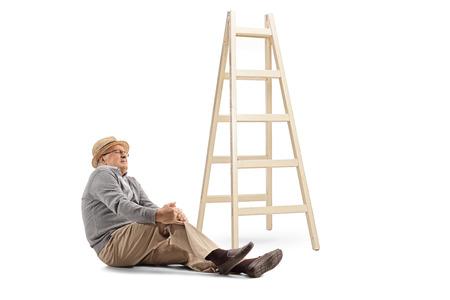 Uomo anziano caduto da una scala seduto sul pavimento e tenendo il ginocchio isolato su sfondo bianco