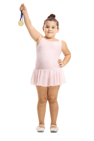 Full length portrait of a little ballerina girl holding a gold medal isolated on white background Imagens