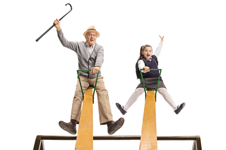 Cheerful grandpa and his granddaughter having fun on a seesaw isolated on white background
