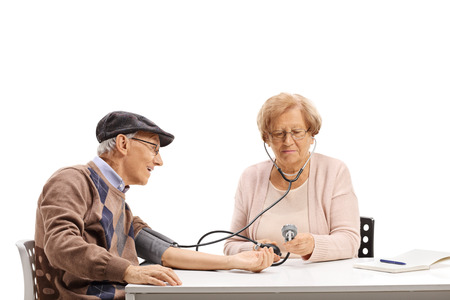 Elderly wife taking blood pressure measurements to her husband isolated on white background