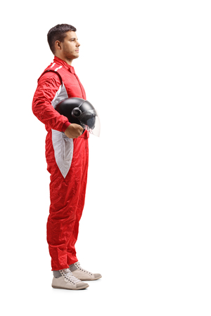 Full length profile shot of a male racer in a red jumpsuit standing and holding a halmet isolated on white background