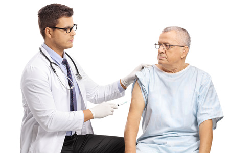 Young doctor vaccinating a mature male patient isolated on white background