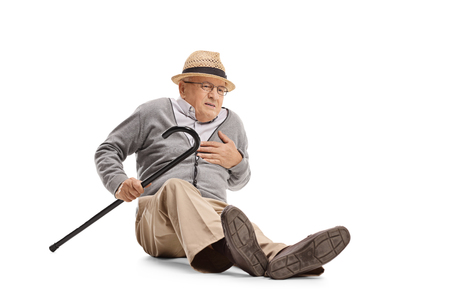Full length shot of an elderly man on the ground having a heart attack isolated on white background