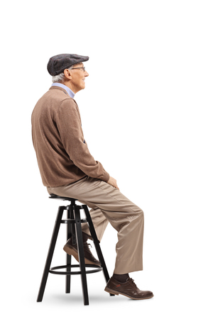 Full length shot of a senior man sitting on a stool chair isolated on white background