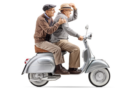 Full length shot of two senior men riding a vintage scooter fast isolated on white background