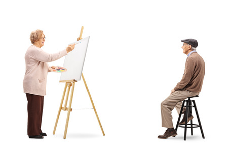 Full length shot of an elderly woman drawing a portrait of senior male model on a canvas isolated on white background