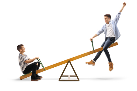 Full length shot of two cheerful teenage boys on a seesaw isolated on white background Standard-Bild