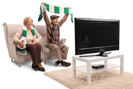 Senior female and male soccer fans cheering with a scarf and watching a game isolated on white background