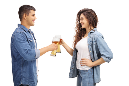 Young man and woman making cheers with glasses of beer isolated on white background