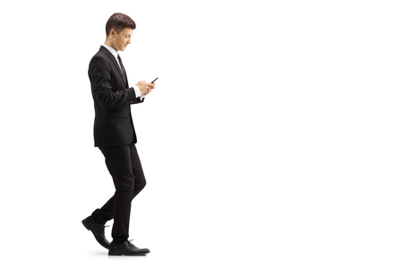 Full length profile shot of a young man in a black suit walking and typing onto a mobile phone isolated on white