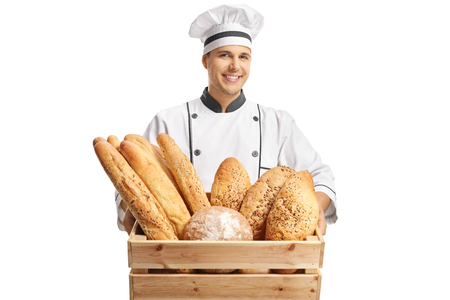 Young male baker holding a box with different types of bread isolated on white