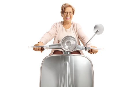 Cheerful senior woman riding a vintage scooter isolated on white