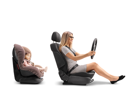 Young woman in a car seat holing a steering wheel and a baby girl strapped in a car seat isolated on white Reklamní fotografie