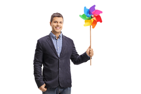 Handsome young man holding a colorful pinwheel and looking at the camera isolated on white background