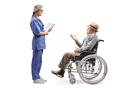 Full length profile shot of a young female nurse talking to an elderly gentleman in a wheelchair isolated on white background 免版税图像