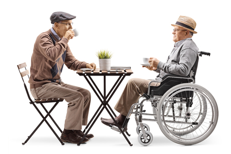 Full length profile shot of a senior man sitting and drinking coffee with a disabled man in a wheelchair isolated on white background