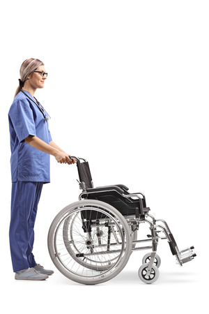 Full length profile shot of a young female nurse with an empty wheelchair isolated on white background