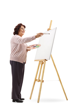 Full length shot of an elderly woman drawing with paint on canvas isolated on white background