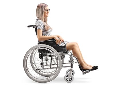 Profile shot of a young blond woman in a wheelchair isolated on white background Imagens