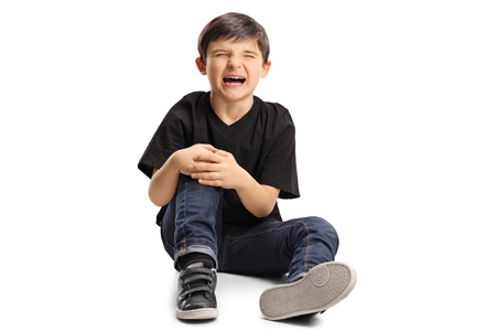 A boy sitting on the floor in pain, holding his knee and crying isolated on white background