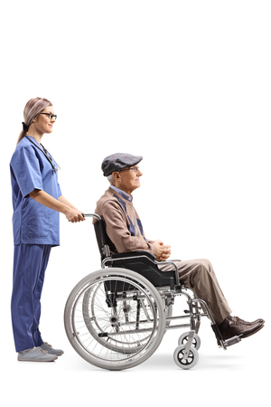 Full length profile shot of a nurse pushing a senior man in a wheelchair isolated on white background