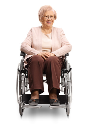 Senior woman sitting in a wheelchair and smiling at the camera isolated on white background