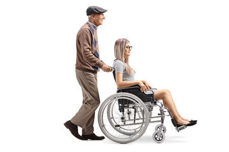 Full length profile shot of an elderly man pushing a young woman in a wheelchair isolated on white background