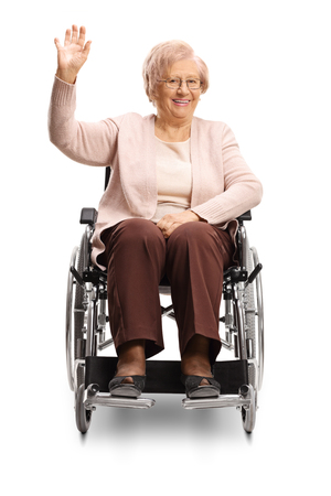 Elderly disabled woman sitting in a wheelchair and waving isolated on white background