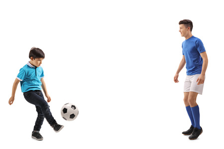 Full length shot of a little boy playing soccer with an older boy isolated on white background 写真素材