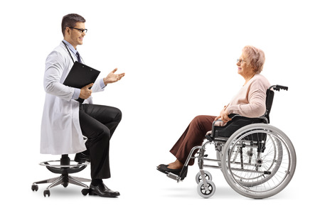 Full length shot of a male doctor talking to a mature female patient in a wheelchair isolated on white background
