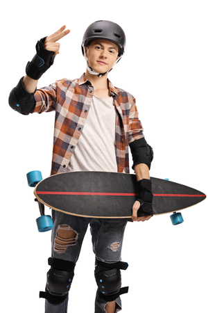 Young boy with a helmet holding a longboard and gesturing a victory sign with his fingers isolated on white background