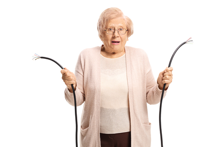 Confused old lady holding a broken cable isolated on white background Stockfoto