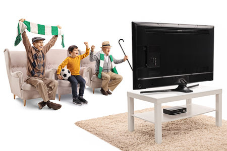 Full length shot of a little boy watching a game on TV with two senior men and cheering isolated on white background