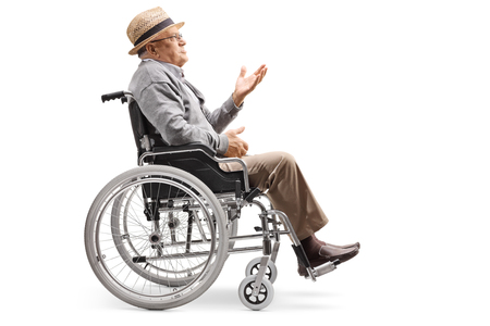 Full length profile shot of an elderly man sitting in a wheelchair and gesturing a conversation isolated on white background Imagens