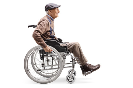 Full length profile shot of a senior man manually riding a wheelchair isolated on white background