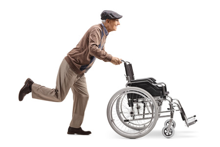 Full length profile shot of an elderly man running and pushing an empty wheelchair isolated on white background Imagens