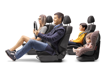Full length shot of a family of four in car seats with a fastened seat belts isolated on white background