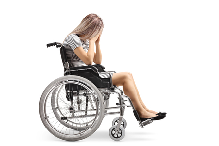Full length shot of a sad young disabled female in a wheelchair holding her head isolated on white background Imagens
