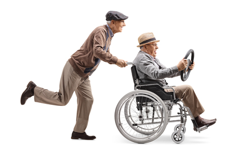 Full length profile shot of an elderly man pushing a man sitting in a wheelchair and holding a steering wheel from a car isolated on white background Imagens