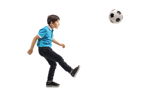 Full length shot of a little boy kicking a soccer ball isolated on white background Banco de Imagens