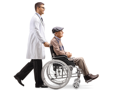 Full length shot of a young male doctor pushing a senior man in a wheelchair isolated on white background