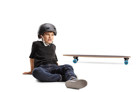 Little boy with helmet sitting on the floor in pain injured from a fall with longboard isolated on white background