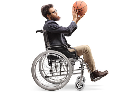 Full length profile shot of a young man in a wheelchair holding a basketball isolated on white background Imagens