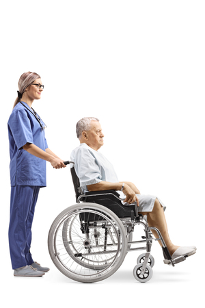 Full length profile shot of a young female nurse pushing an elderly male patient in a wheelchair isolated on white background