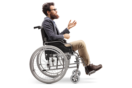 Full length profile shot of a young man in a wheechair gesturing with hand isolated on white background Imagens