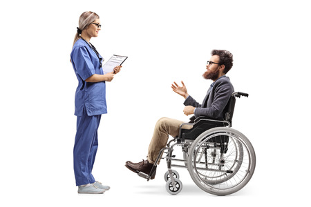 Full length profile shot of a young female nurse talking to a bearded man in a wheelchair isolated on white background