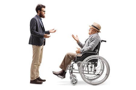 Full length profile shot of a young man talking to an elderly gentleman in a wheelchair isolated on white background Imagens