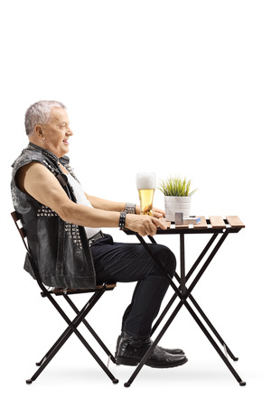 Full length profile shot of an old punk man sitting at a table and drinking beer isolated on white background