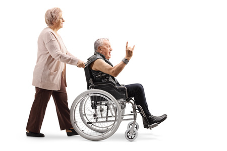 Full length profile shot of an elderly woman pushing a mature man making a rock and roll hand sign in a wheelchair isolated on white background